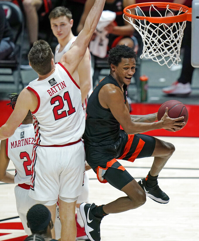 Oregon State guard Gianni Hunt, right, goes to the basket as Utah forward Riley Battin (21) defends during the second half during an NCAA college basketball game Wednesday, March 3, 2021, in Salt Lake City. (AP Photo/Rick Bowmer)