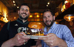 "In this May 8, 2019 photo, Lou Liapis, left, and brother Pete Liapis hold the ""Gyro Step"" at their restaurant Georgie Porgie's in Oak Creek, Wis. They created the Greek-inspired sandwich, which includes a burger patty, gyro meat, feta cheese and tzatziki sauce, in honor of the fancy footwork of Bucks star Giannis Antetokuonmpo, who was born in Greece. It will be available during the playoffs. (AP Photo/Carrie Antlfinger)"