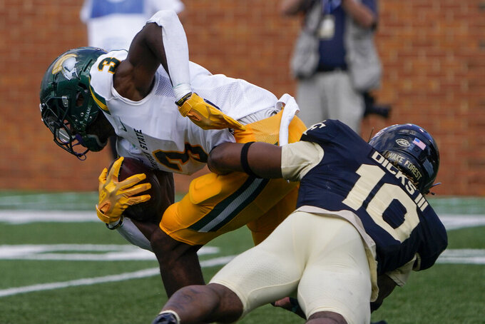 Norfolk State wide receiver Justin Smith is tackled by Wake Forest defensive back Kenneth Dicks III during the second half of a NCAA college football game Saturday, Sept. 11, 2021, in Winston-Salem, N.C. (AP Photo/Chris Carlson)