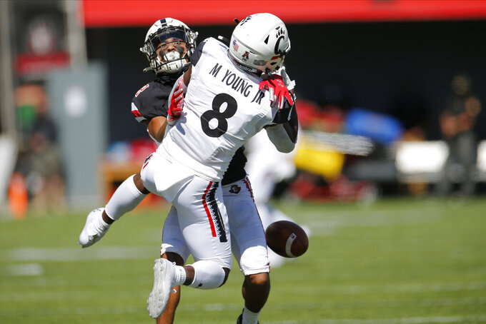 Austin Peay defensive back Nathan Page, rear, interferes with Cincinnati receiver Michael Young during the second half of an NCAA college football game Saturday, Sept. 19, 2020, in Cincinnati, Ohio. Page was penalized on the play. Cincinnati beat Austin Peay 55-20. (AP Photo/Jay LaPrete)