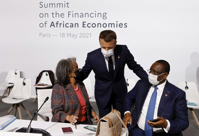 rench President Emmanuel Macron, center, salutes Ethiopia's President Sahle-Work Zewde, left, and Senegal's President Macky Sall at the Summit on the Financing of African Economies Tuesday, May 18, 2021 in Paris. More than twenty heads of state and government from Africa are holding talks in Paris with heads of international organizations on how to revive the economy of the continent, deeply impacted by the consequences of the COVID-19 pandemic. (Photo by Ludovic Marin, Pool via AP)