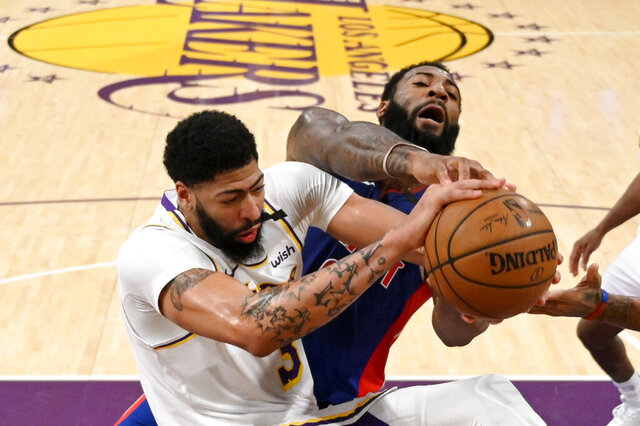 Los Angeles Lakers forward Anthony Davis, left, and Detroit Pistons center Andre Drummond grapple for the ball during the first half of an NBA basketball game Sunday, Jan. 5, 2020, in Los Angeles. (AP Photo/Mark J. Terrill)