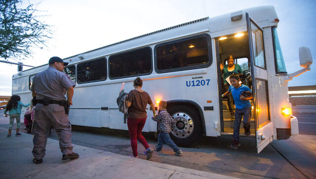 FILE - In this May 28, 2014, file photo, migrants are released from ICE custody at a Greyhound bus station in Phoenix. Greyhound, the nation's largest bus company, says it will stop allowing Border Patrol agents without a warrant to board its buses to conduct routine immigration checks. The company announced the change Friday, Feb. 21, 2020, one week after The Associated Press reported on a leaked Border Patrol memo confirming that agents can't board private buses without the consent of the bus company. (Michael Chow/The Arizona Republic via AP, File)