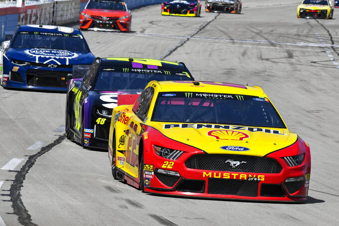 Joey Logano (22) takes the lead from Jimmie Johnson (48) during a NASCAR Cup auto race at Texas Motor Speedway, Sunday, March 31, 2019, in Fort Worth, Texas. (AP Photo/Larry Papke)