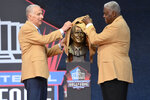 Paul Tagliabue, a member of the Pro Football Hall of Fame Centennial Class, and a former NFL commissioner, unveils his bust with presenter Art Shell during the induction ceremony at the Pro Football Hall of Fame, Saturday, Aug. 7, 2021, in Canton, Ohio. (AP Photo/David Richard)