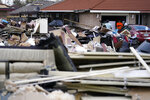 Residents take a break from gutting their flooded homes as debris piles at curbside in the aftermath of Hurricane Ida in LaPlace, La., Tuesday, Sept. 7, 2021. (AP Photo/Gerald Herbert)