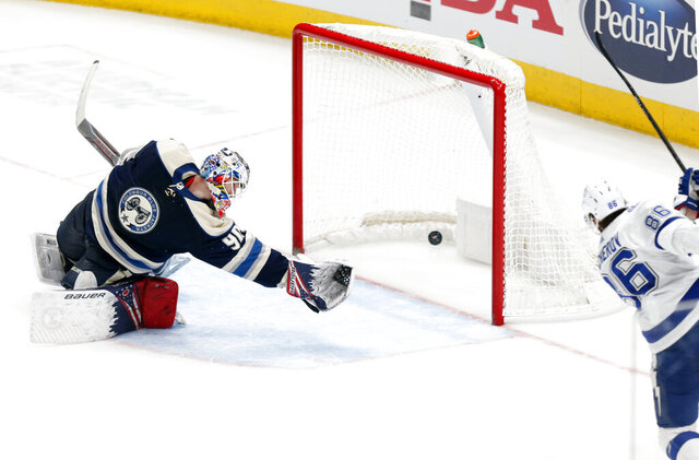 Tampa Bay Lightning forward Nikita Kucherov, right, of Russia, scores the winning goal past Columbus Blue Jackets goalie Elvis Merzlikins, of Latvia, during an overtime period of an NHL hockey game in Columbus, Ohio, Monday, Feb. 10, 2020. (AP Photo/Paul Vernon)