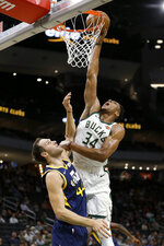 Milwaukee Bucks' Giannis Antetokounmpo (34) dunks over Utah Jazz's Bojan Bogdanovic during the first half of a preseason NBA basketball game Wednesday, Oct. 9, 2019, in Milwaukee. (AP Photo/Aaron Gash)