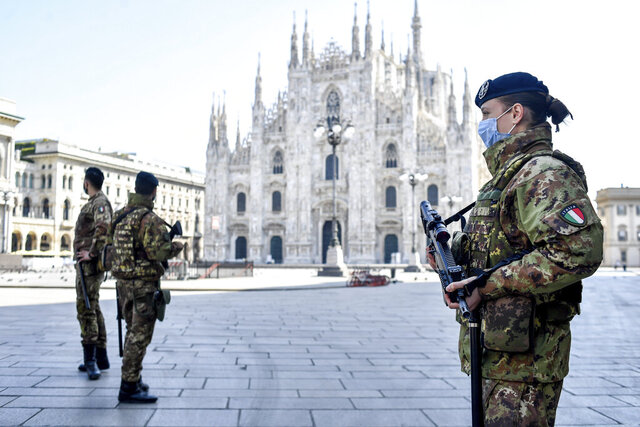 Soldiers patrol in front of the Duomo gothic cathedral in Milan, Italy, Sunday, April 5, 2020. The government is demanding Italians stay home and not take the leveling off of new coronavirus infections as a sign the emergency is over, following evidence that more and more Italians are relaxing restrictions the west's first and most extreme nationwide lockdown and production shutdown. (Claudio Furlan/LaPresse via AP)