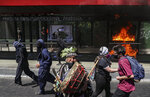 An Indigenous Mapuche man plays a kultrun drum near a bus stop set fire by protesters after police blocked the route of a march against the the discovery of the Americas so it could not pass the presidential palace in Santiago, Chile, Monday, Oct. 12, 2020. The march was organized by Indigenous groups demanding autonomy and the recovery of ancestral land. (AP Photo/Esteban Felix)