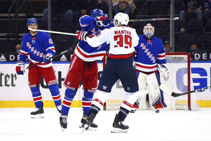 New York Rangers' Pavel Buchnevich (89) hits Washington Capitals' Anthony Mantha (39) with his stick during the second period of an NHL hockey game Wednesday, May 5, 2021, in New York. Buchnevich was penalized for high-sticking. (Bruce Bennett/Pool Photo via AP)