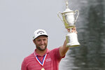 Jon Rahm, of Spain, holds the champions trophy for photographers after the final round of the U.S. Open Golf Championship, Sunday, June 20, 2021, at Torrey Pines Golf Course in San Diego. (AP Photo/Jae C. Hong)