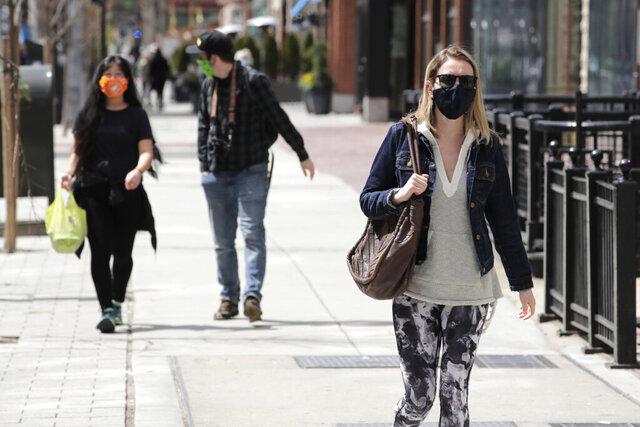 Pedestrians, wearing masks due to the coronavirus outbreak, walk down Boylston Street in Boston, Wednesday, April 15, 2020. (AP Photo/Charles Krupa)