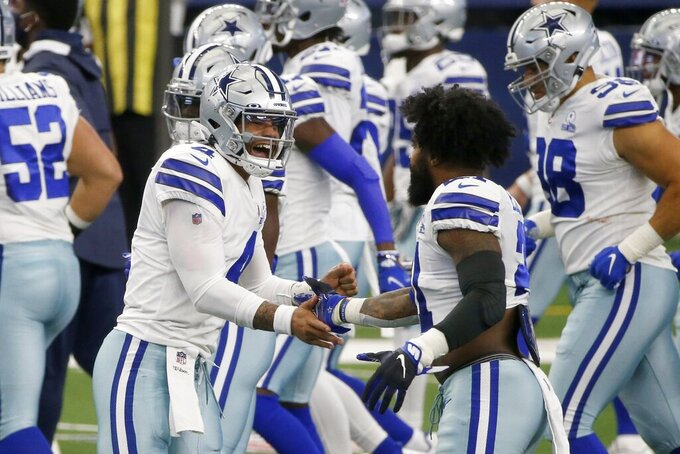 Dallas Cowboys' Dak Prescott (4) and Ezekiel Elliott, right, greet each other on the field during an NFL football game against the Atlanta Falcons in Arlington, Texas, Sunday, Sept. 20, 2020. (AP Photo/Michael Ainsworth)