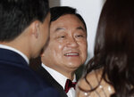 Former Thai Prime Minister Thaksin Shinawatra, center, chats with guests for his daughter's wedding at a hotel in Hong Kong, Friday, March 22, 2019. (AP Photo/Kin Cheung)