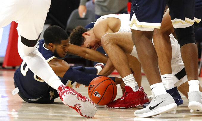 North Carolina State's Jericole Hellems (4) and Charleston Southern's Travis Anderson, left, go after a loose ball during an NCAA college basketball game in Raleigh, N.C., Wednesday, Nov. 25, 2020. (Ethan Hyman/The News & Observer via AP)