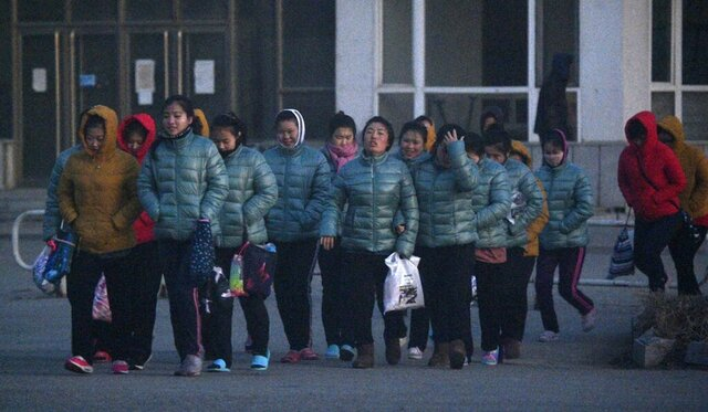 In this Dec. 5, 2019, photo, North Korean factory workers head to work before dawn in Dandong, a Chinese city on the border with North Korea. A U.N.-set deadline for member states to repatriate all North Korean workers on their soils falls on Sunday, Dec. 22. The estimate for the number of North Koreans working in China has been as high as 50,000 to 80,000, with the vast majority working in factories the country's northeast along the long border with North Korea. China hosts the most North Korean workers. (Kyodo News via AP)