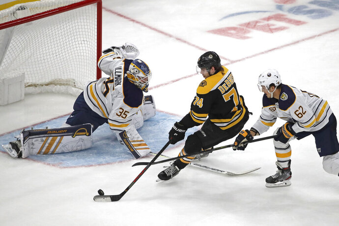 Boston Bruins left wing Jake DeBrusk (74) can't score against the defense of Buffalo Sabres' Brandon Montour (62) and Sabres goaltender Linus Ullmark (35) during the second period of an NHL hockey game, Thursday, Nov. 21, 2019, in Boston. (AP Photo/Elise Amendola)