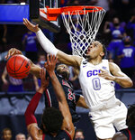 Grand Canyon's Sean Miller-Moore (0) is fouled by New Mexico State's William McNair (24) during the first half of an NCAA college basketball game for the championship of the Western Athletic Conference men's tournament Saturday, March 13, 2021, in Las Vegas. (AP Photo/Chase Stevens)