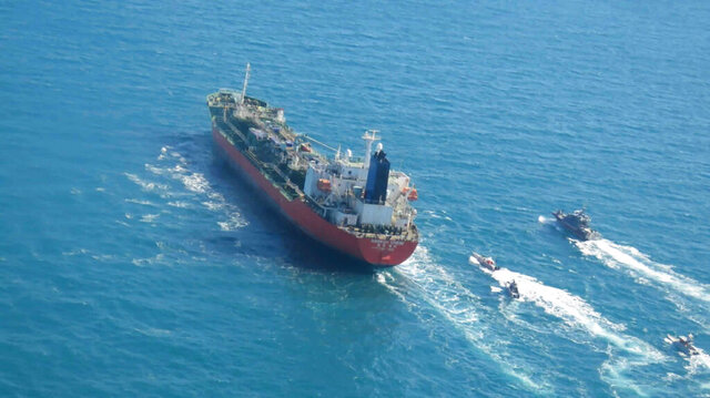 """In this photo released Monday, Jan. 4, 2021, by Tasnim News Agency, a seized South Korean-flagged tanker is escorted by Iranian Revolutionary Guard boats on the Persian Gulf. Iranian state television acknowledged that Tehran seized the oil tanker in the Strait of Hormuz. The report on Monday alleged the MT Hankuk Chemi had been stopped by Iranian authorities over alleged """"oil pollution"""" in the Persian Gulf and the strait. (Tasnim News Agency via AP)"""
