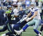FILE - In this Sept. 23, 2018, file photo, Seattle Seahawks free safety Earl Thomas, left, reaches for a pass he intercepted that was intended for Dallas Cowboys tight end Blake Jarwin, right, during the second half of an NFL football game in Seattle. The pick was Thomas' second of the game. Thomas, whom Cowboys owner Jerry Jones has coveted for years, should become a leader in the Cowboys' secondary and locker room, and will never give less than his all. (AP Photo/John Froschauer, File)