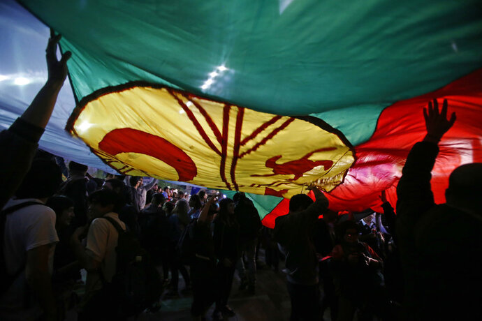 FILE - In this Sept. 26, 2017 photo, demonstrators sustain afloat the Mapuche nation's flag during a protest against the arrests of several Mapuches, in Santiago, Chile. Pope Francis will meet with indigenous groups during his Chile, Peru visit beginning Jan. 15, 2018. The Chilean stop is more delicate as the visit comes as some radical Mapuche groups have been staging violent protests, occupying and burning farms, churches and lumber trucks to demand the return of their land. (AP Photo/Luis Hidalgo, File)
