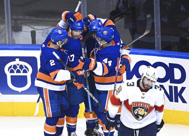 New York Islanders left wing Matt Martin (17) celebrates his goal with teammates as Florida Panthers defenceman Keith Yandle (3) skates away during the second period of an NHL Stanley Cup playoff hockey game in Toronto, Tuesday, Aug. 4, 2020. (Nathan Denette/The Canadian Press via AP)