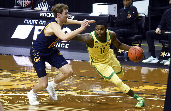 Oregon guard Amauri Hardy (11) drives past California guard Ryan Betley (00) during the second half of an NCAA college basketball game Thursday, Dec. 31, 2020, in Eugene, Ore. (AP Photo/Andy Nelson)