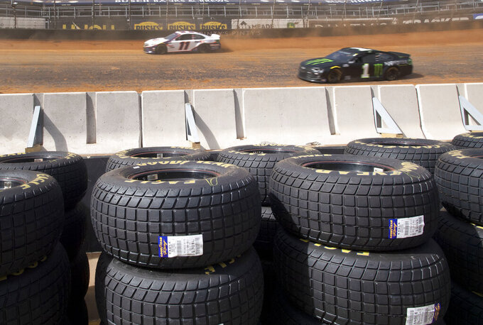 With the new Goodyear Eagle dirt tires stacked along the infield wall, Denny Hamlin and Kurt Busch drive on the dirt track during NASCAR Cup Series practice, Friday, March 26, 2021, at Bristol Motor Speedway in Bristol, Tenn. (David Crigger/Bristol Herald Courier via AP)