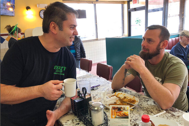 Gino Zoto, left, owner of Earl's Diner in Ferndale, Mich., talks to customer Oren Freel on Monday, March 16, 2020. Michigan is limiting restaurants to carry-out orders only as of 3 pm Monday.