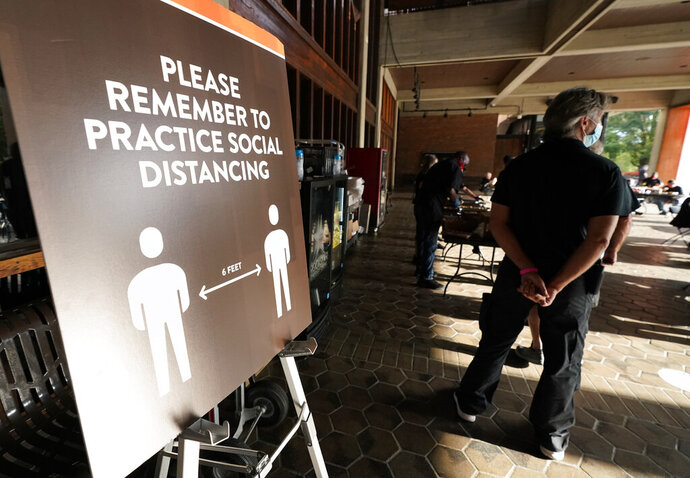 Event staff stand at the entrance to the Grand Ole Opry House near signs encouraging social distancing during the 55th annual Academy of Country Music Awards on Wednesday, Sept. 16, 2020, in Nashville, Tenn. (AP Photo/Mark Humphrey)