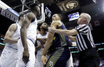 Marquette forward Theo John, center right, is held back by an official as he argues with Seton Hall forward Michael Nzei, second from left, during the first half of an NCAA college basketball game, Wednesday, March 6, 2019, in Newark, N.J. (AP Photo/Julio Cortez)