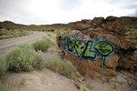 ARCHIVO - En esta fotografía del 22 de julio de 2019 se muestra un graffiti con temática de aliens sobre una roca de una carretera de Rachel, Nevada, una localidad cercana al Área 51. (AP Foto/John Locher, Archivo)