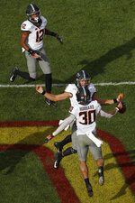 Oklahoma State quarterback Spencer Sanders, center, celebrates with Oklahoma State running back Chuba Hubbard, bottom, after Hubbard scored a touchdown against Iowa State during the first half of an NCAA college football game, Saturday, Oct. 26, 2019, in Ames, Iowa. (AP Photo/Matthew Putney)