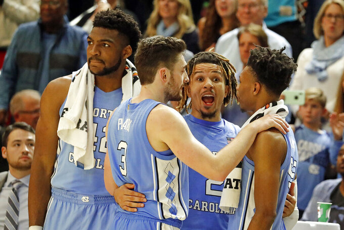 North Carolina's Cole Anthony (2) celebrates with teammates Christian Keeling, right, Andrew Platek (3), and Brandon Huffman (42) during the second half of an NCAA college basketball game against North Carolina Wilmington in Wilmington, N.C., Friday, Nov. 8, 2019. (AP Photo/Karl B DeBlaker)