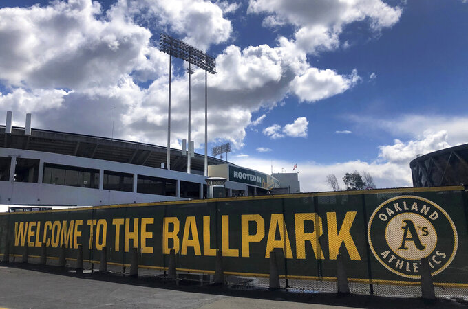 FILE — In this March 25, 2020, file photo a banner has a welcome message to Oakland Athletics fans at the Oakland-Alameda County Coliseum in Oakland, Calif. The Oakland City Council approved Tuesday, July 20, 2021, preliminary terms for a new $12 billion waterfront ballpark project for the Athletics. But it's not clear if the 6-1 vote will be enough to keep the A's at the negotiating table instead of leaving the city. (AP Photo/Ben Margot,File)