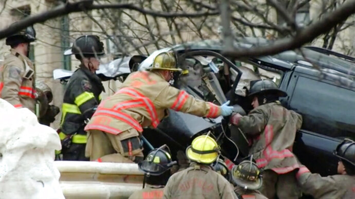 This still image provided by WKBW.COM shows firefighters trying to open a minivan door after it crashed into a monument in Buffalo, N.Y., on Thursday, Nov. 26, 2020.  Police on Friday were investigating what led a speeding minivan to crash into a monument in front of Buffalo City Hall, killing a passenger and seriously injuring the driver on Thanksgiving.  (WKBW.COM via AP)