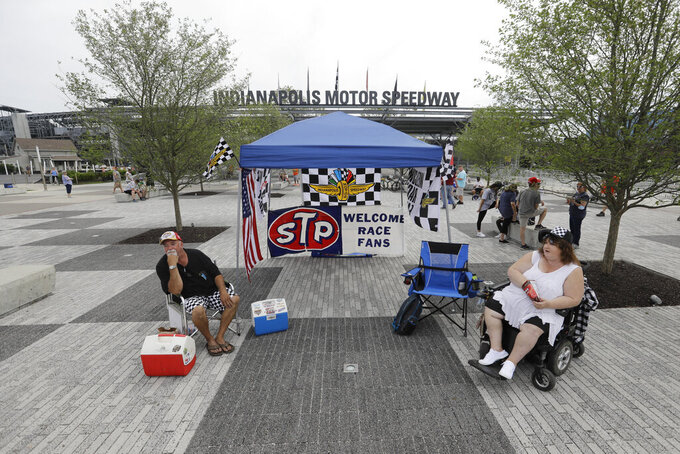 Jeff and Diana Blackford sit outside of the main gate at Indianapolis Motor Speedway, Sunday, May 24, 2020, in Indianapolis. The Indianapolis 500 was postponed to Aug. 23 due to the coronavirus outbreak. (AP Photo/Darron Cummings)