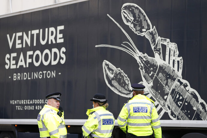 Police speak to a shellfish export truck driver as he is stopped for an unnecessary journey in London, Monday, Jan. 18, 2021, during a demonstration by British Shellfish exporters to protest Brexit-related red tape they claim is suffocating their business. The drivers were later stopped by police and issued with fines for an 'unnecessary journey' due to the national lockdown to curb the spread of the coronavirus. (AP Photo/Alastair Grant)