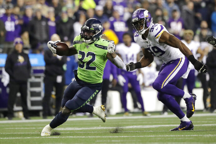 Seattle Seahawks' Chris Carson runs on a 26-yard carry as Minnesota Vikings' Danielle Hunter pursues during the second half of an NFL football game, Monday, Dec. 2, 2019, in Seattle. (AP Photo/Ted S. Warren)