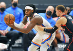 Oklahoma City Thunder's Lugeuntz Dort, left, looks to pass the ball under pressure from Toronto Raptors' Malachi Flynn, right, during the half of a basketball game Sunday, April 18, 2021, in St. Petersburg, Fla. (AP Photo/Steve Nesius)