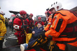 Fire and Rescue service members lift a man onto an inflatable boat that has been used to rescue residents trapped by floodwater in in Doncaster, northern England, Friday, Nov. 8, 2019. Torrential rain drenched parts of north and central England, swelling rivers, forcing evacuations and disrupting travel. One woman died after being swept away by surging waters. (Danny Lawson/PA via AP)