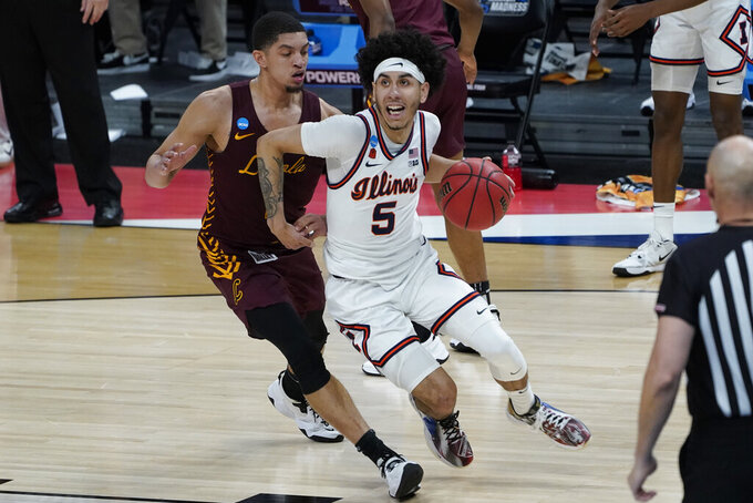 Illinois guard Andre Curbelo (5) drives on Loyola Chicago guard Lucas Williamson (1) during the first half of a men's college basketball game in the second round of the NCAA tournament at Bankers Life Fieldhouse in Indianapolis, Sunday, March 21, 2021. (AP Photo/Paul Sancya)