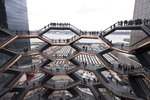 FILE - In this March 15, 2019, file photo, visitors to the Vessel climb its staircases on its opening day at Hudson Yards in New York.  Officials are evaluating the future of the 150-foot-tall piece of public art in New York City after a string of suicides.  (AP Photo/Mark Lennihan, File)