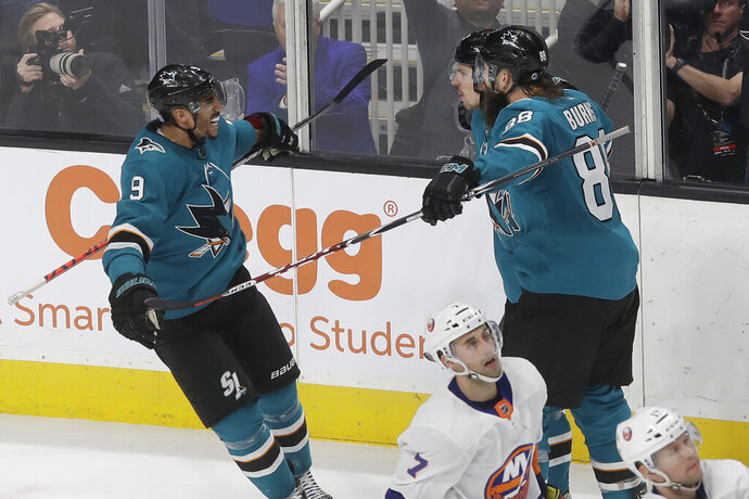 San Jose Sharks center Logan Couture, right rear, is congratulated by left wing Evander Kane (9) and defenseman Brent Burns, front right, after scoring against the New York Islanders during overtime in an NHL hockey game in San Jose, Calif., Saturday, Nov. 23, 2019. The Sharks won 2-1. (AP Photo/Jeff Chiu)
