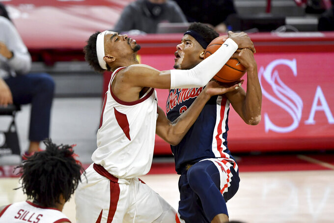Mississippi guard Devontae Shuler (2) is fouled by Arkansas defender Jalen Tate (11) as he tries to drive to the hoop during the second half of an NCAA college basketball game Wednesday, Jan. 27, 2021, in Fayetteville, Ark. (AP Photo/Michael Woods)