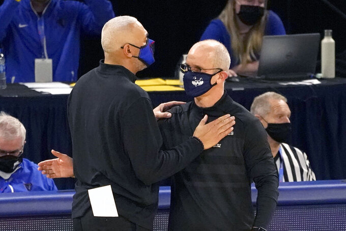 DePaul head coach Dave Leitao, left, and Connecticut head coach Dan Hurley meet at half court after an NCAA college basketball game Monday, Jan. 11, 2021, in Chicago. (AP Photo/Charles Rex Arbogast)
