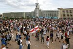 People, many holding old Belarusian national flags as they gather at Independent Square in the center of Minsk, Belarus, Friday, Aug. 14, 2020. Some thousands of people flooded the centre of the Belarus capital, Minsk, in a show of anger over a brutal police crackdown this week on peaceful protesters that followed a disputed election. (AP Photo/Sergei Grits)