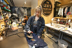 FILE - In this June 14, 2019, file photo tailors Latoya Henderson, left, and Aly Reinert work in the Levi's Tailor Shop, in the Levi's store, in New York's Times Square. Levi Strauss & Co. reports earns Tuesday, Oct. 8. (AP Photo/Richard Drew, File)
