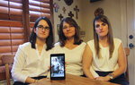 FILE - In this Feb. 15, 2019 file photo, Dennysse Vadell sits between her daughters Veronica, right, and Cristina holding a digital photograph of father and husband Tomeu who is currently jailed in Venezuela, in Katy, Texas. Tomeu Vadell, who is one of six U.S. oil executive jailed for three years in Venezuela, says in a letter from prison provided to The Associated Press on Tuesday, Nov. 24, 2020, that it's especially painful to be separated during the Thanksgiving season from from his wife, three adult children and a newborn grandson he's never held.  (AP Photo/John L Mone, File)